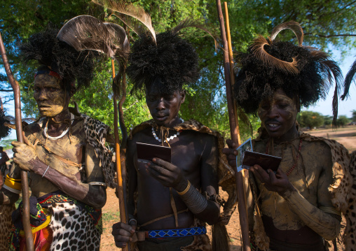 Dassanech tribe men looking polaroid pictures of themselves, Omo valley, Omorate, Ethiopia