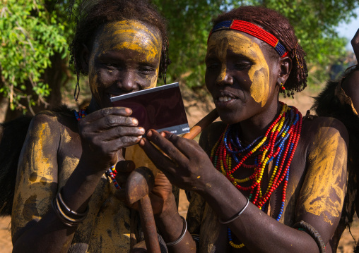 Dassanech tribe women looking polaroid pictures of themselves, Omo valley, Omorate, Ethiopia