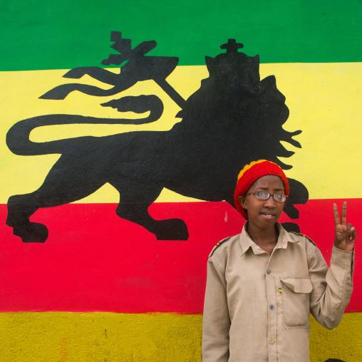 Rastafari girl called kizzy in front of a lion of judah mural, Oromo, Shashamane, Ethiopia