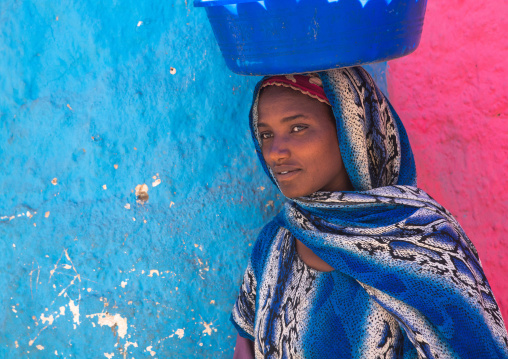 Harari woman carrying a bassin on her head in the street, Harari region, Harar, Ethiopia