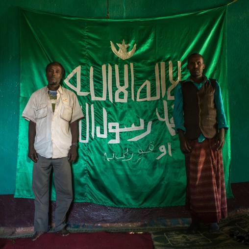 Sufi men worshippers in front of islamic flag, Harari region, Harar, Ethiopia