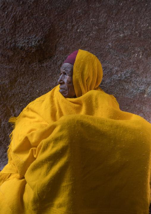 Portrait of a monk woman in yellow shawl during kidane mehret celebration, Amhara region, Lalibela, Ethiopia