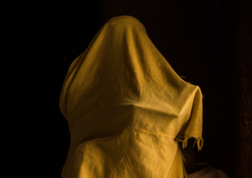 Orthodox woman covered with a yellow shawl praying with a bible, Amhara region, Lalibela, Ethiopia