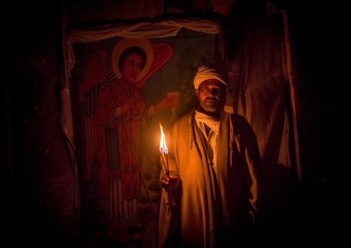 Ethiopian priest holding a candle during kidane mehret orthodox celebration, Amhara region, Lalibela, Ethiopia