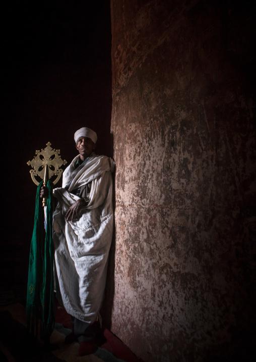 Ethiopian orthodox priest holding a cross inside a rock church, Amhara region, Lalibela, Ethiopia
