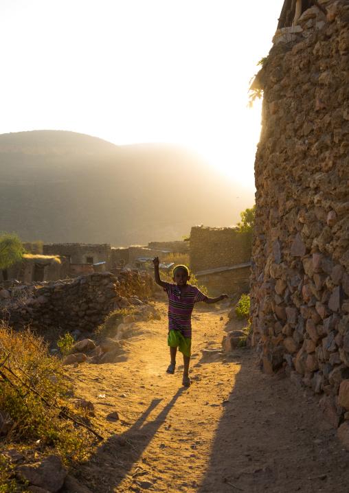 Ethiopian boy running in the streets of a traditional Argoba stone houses village near harar, Harari Region, Koremi, Ethiopia