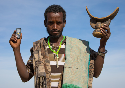 Issa tribe man holding a mobile phone and a wooden pillow, Afar region, Yangudi Rassa National Park, Ethiopia