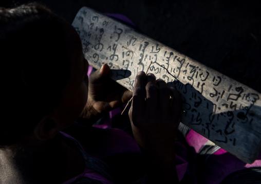 Afar tribe girl writing on a wood board in a coranic school, Afar region, Afambo, Ethiopia