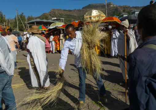 Ethiopian man putting straw on the path of the priests who will carry tabots during Timkat epiphany festival, Amhara region, Lalibela, Ethiopia