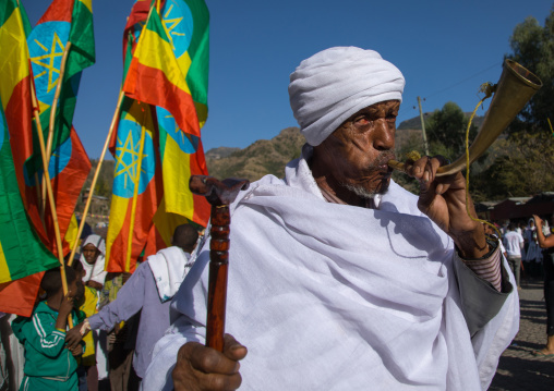 Ethiopian orthodox priest blowing in a horn during the colorful Timkat epiphany festival, Amhara region, Lalibela, Ethiopia