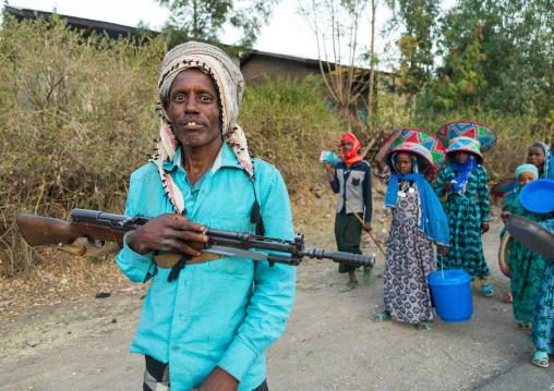 Ethiopian man with a gun and women carrying gifts during an Oromo wedding celebration, Amhara region, Artuma, Ethiopia