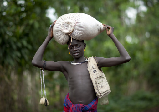 Young menit man carrying a sack on his head, Tum market, Omo valley, Ethiopia