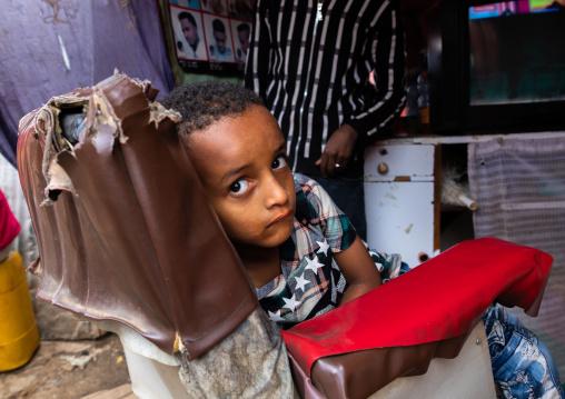 Ethiopian boy sit on a barber seat, Harari region, Harar, Ethiopia