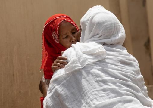 Muslim woman kissing an orthodox woman in the street, Harari region, Harar, Ethiopia