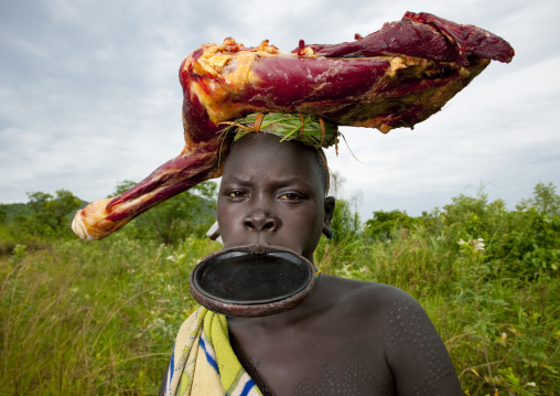 Surma Girl With A Lip Plate Wearing Cow Meat On Her Head, Omo Valley, Ethiopia