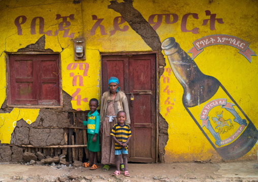 Ethiopian family standing in front of an old beer advertising painted on a wall, Omo valley, Jinka, Ethiopia