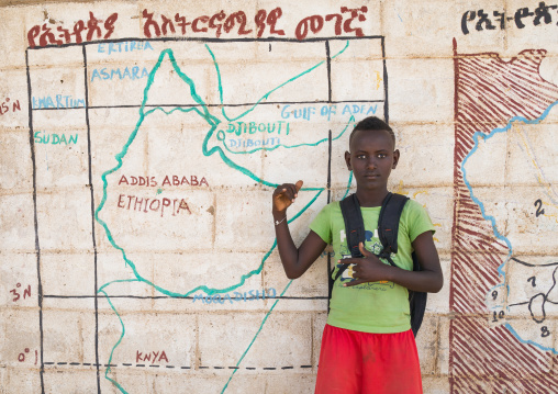 Nyangatom tribe boy in front of a school mural depicting the map of east africa, Omo valley, Kangate, Ethiopia
