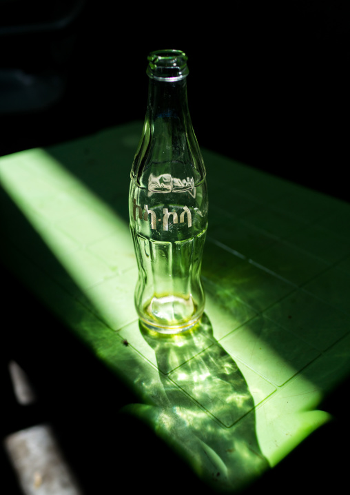 Ethiopian coca cola bottle in a ray of light in a bar, Omo Valley, Kangate, Ethiopia