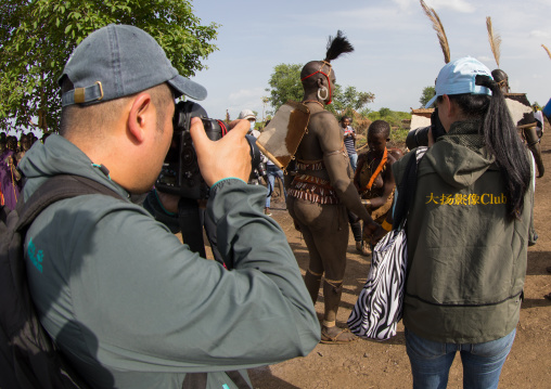 Chinese tourists taking pictures of Bodi tribe fat men during Kael ceremony, Omo valley, Hana Mursi, Ethiopia