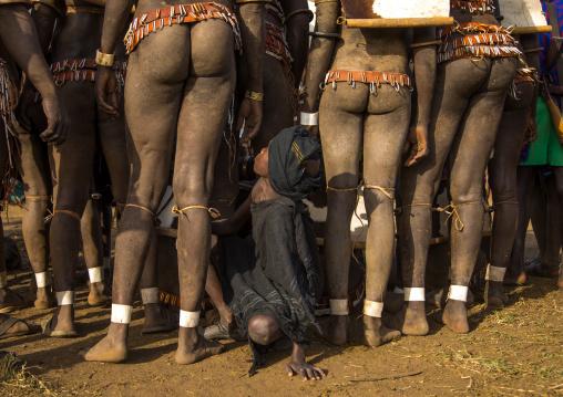 Child boy in the middle of Bodi tribe fat men legs during Kael ceremony, Omo valley, Hana Mursi, Ethiopia