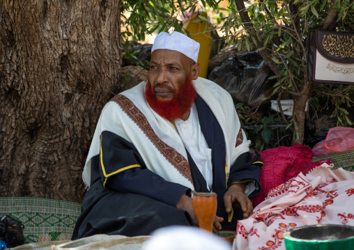 Imam with red beard chewing khat during a sufi celebration, Harari Region, Harar, Ethiopia