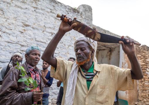Harari man dancing with a huge knife during a sufi celebration, Harari Region, Harar, Ethiopia