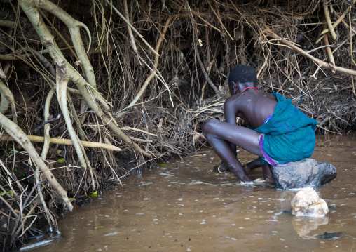 Suri tribe girls doing gold panning in a river, Omo valley, Kibish, Ethiopia