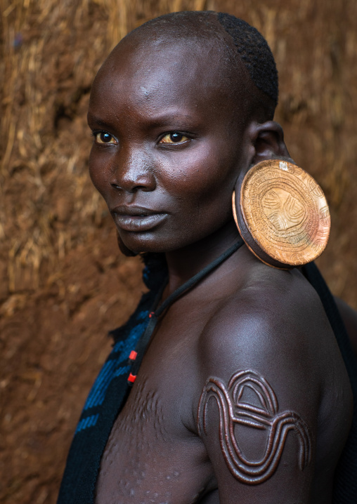 Portrait of a suri tribe woman with enlarged earlobes and huge earrings, Omo valley, Kibish, Ethiopia