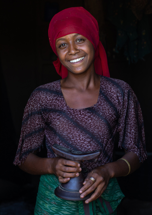 Portrait of a smiling raya tribe girl holding a wooden pillow, Afar Region, Chifra, Ethiopia