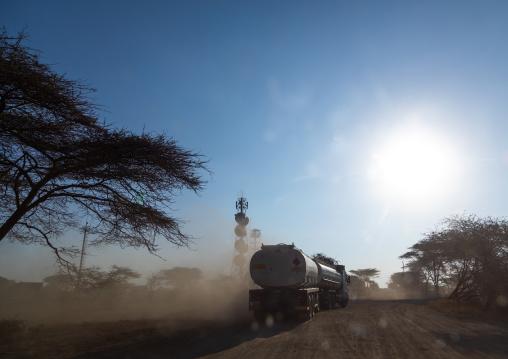 Trucks coming from djibouti port on a dusty road, Oromia, Awash, Ethiopia