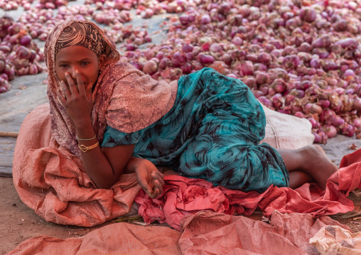 Ethiopian woman lying on the floor and selling oinions, Oromia, Hirna, Ethiopia