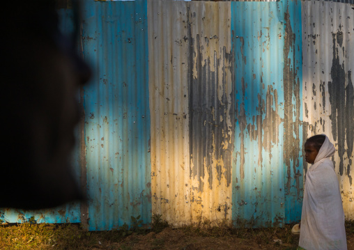 Ethiopian woman passing in front a metalic fence, Addis Ababa Region, Addis Ababa, Ethiopia