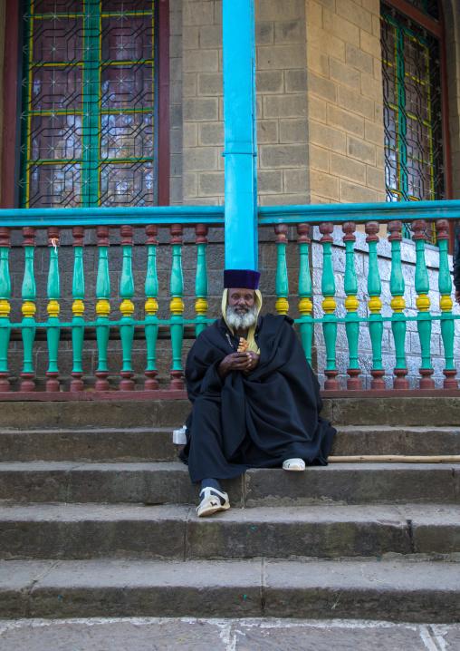 Priest sit on the stairs of the Entoto orthodox Maryam Church, Addis Ababa Region, Addis Ababa, Ethiopia