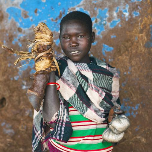 Woman from menit tribe holding an animal's leg, Jemu, Omo valley, Ethiopia