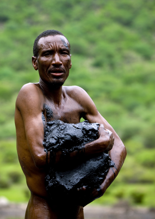 Borana Tribe Man Getting Out Of The Crater Lake Of El Sod Volcano With Volcanic Mud In The Arms, Omo Valley, Ethiopia