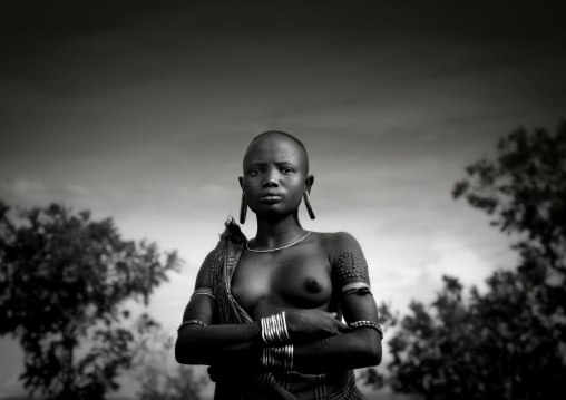 Black And White Portrait Of A Mursi Tribe Woman With Ear Plates And Scarifications, Omo Valley Ethiopia