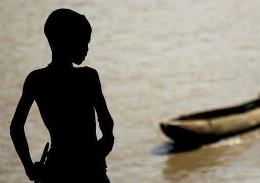 Silhouette Of A Kid Looking At Trunk Boat Used To Cross The Omo River, Omorate, Omo Valley, Ethiopia