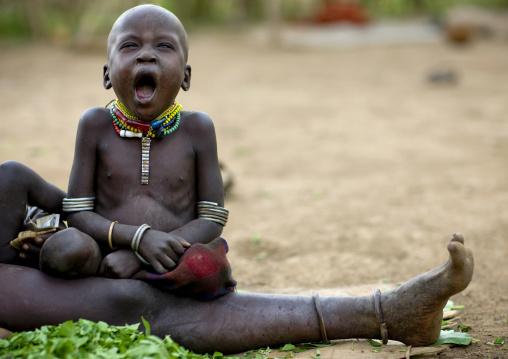 Portrait Of A Tired Nyangatom Baby Yawning, Omo Valley, Kangate, Ethiopia