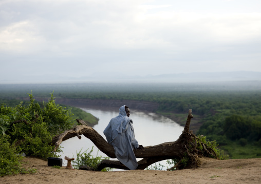 Karo Tribe Man In The Morning Sitting On A Tree Trunk Over The Omo River, Korcho Village, Omo Valley, Ethiopia