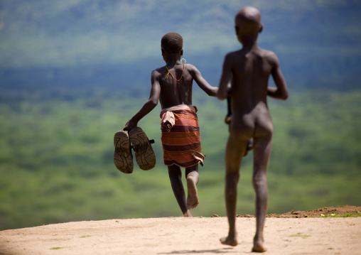 Karo Young Boys Running With Giant Shoes In Hand Ethiopia