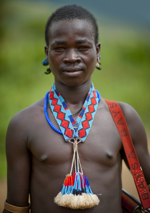 Portrait of a tsemay tribe young man wearing beaded jewels, Omo valley, Ethiopia