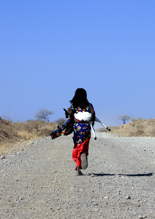 Afar girl carrying a goat, Assaita, Afar regional state, Ethiopia