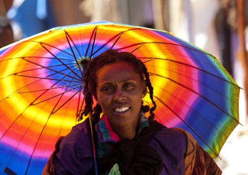 Woman under a rainbow umbrella portrait, Ethiopia
