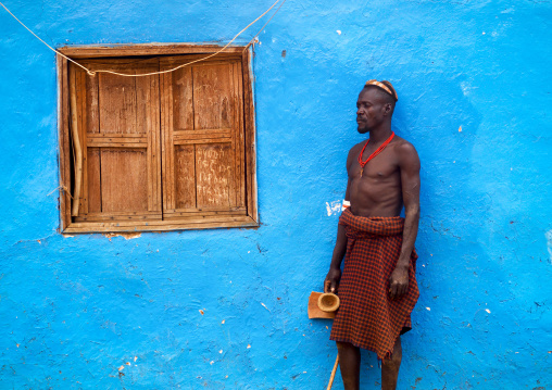 Portrait Of A Dassanech Tribe Man With Headrest Posing Outside A Blue Painted House, Omorate, Omo Valley, Ethiopia