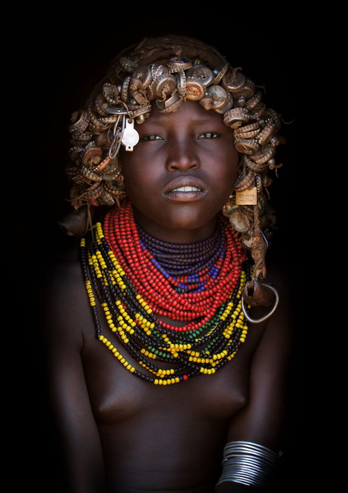 Portrait Of A Dassanech Tribe Girl With Wig Made Of Caps And Traditional Necklaces, Omorate, Omo Valley, Ethiopia