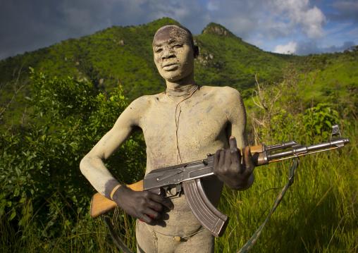 Suri tribe man with body paintings posing with a kalashnikov, Omo valley, Ethiopia