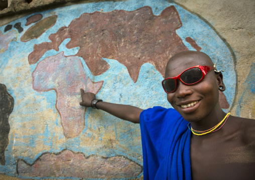 Suri man showing ethiopia on a map of africa in a school, Tulgit, Omo valley, Ethiopia