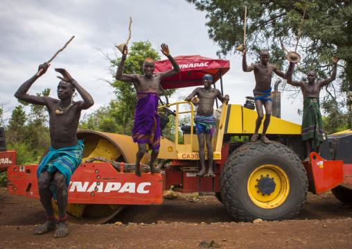 Bodi Tribe Warriors Proudly Jumping From A Bulldozer Near Hana Mursi, Omo Valley, Ethiopia