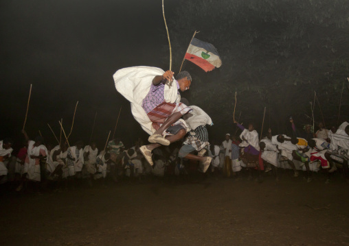 Night Shot Of Two Karrayyu Tribe Men Jumping High During A Choreographed Stick Fighting Dance At Gadaaa Ceremony, Metahara, Ethiopia