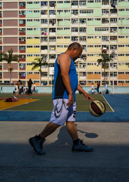 Chinese man playing basket ball in Choi Hung rainbow building, Kowloon, Hong Kong, China